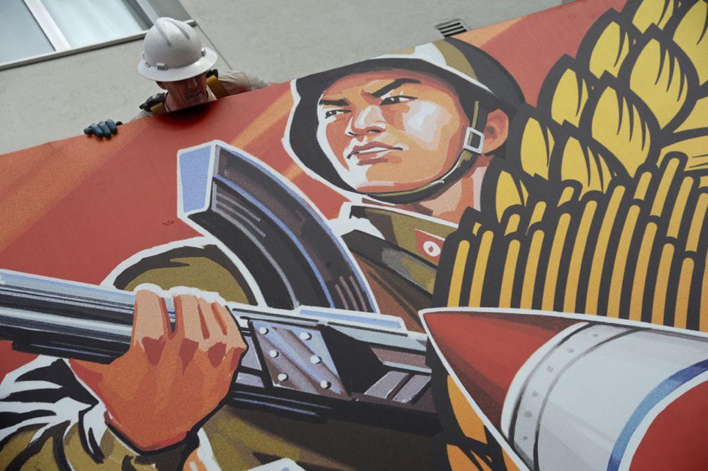 Рабочий снимает плакат для интервью, после того как сети кинотеатров отказались его показывать