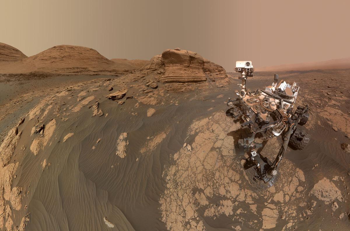 Селфи Curiosity на фоне Mont Mercou: панорама состоит из 60 изображений с камеры MAHLI на манипуляторе марсохода, а также 11 изображений с камеры Mastcam на мачте или «голове» марсохода.