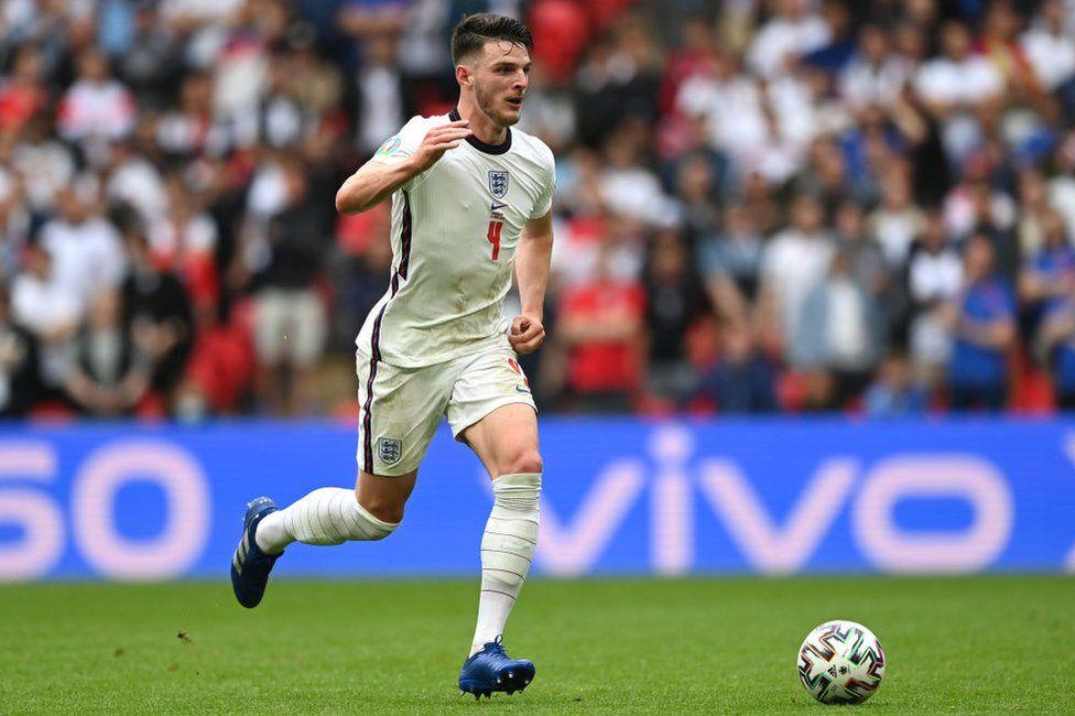 Полузащитник сборной Англии Деклан Райс с рекламой бренда Vivo для смартфонов за спиной.
