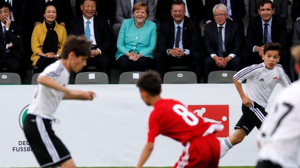 Си Цзиньпин наслаждался игрой в молодежный футбол между Китаем и Германией во время визита в Берлин в 2017 году.