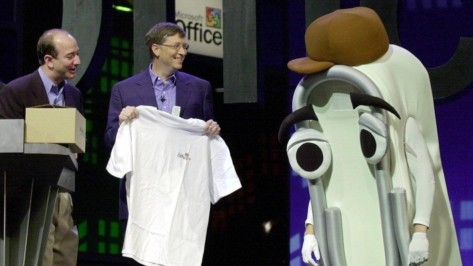 Microsoft co-founder Bill Gates presents Clippy with a retirement gift, a human-sized Office XP T-shirt, in 2001, as Amazon head Jeff Bezos watches