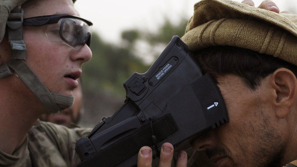 A US solider collects biometric information from a villager in 2012